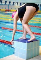 kvinna i början av simning foto
