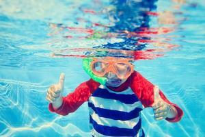söt liten pojke som simmar under vattnet foto