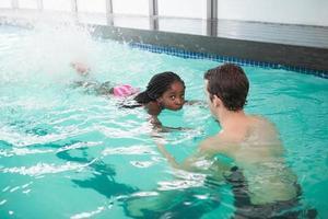 söt liten flicka som lär sig att simma med tränaren foto