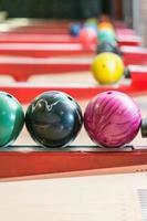 färgglada bowlingbollar på rack selektiv fokus foto