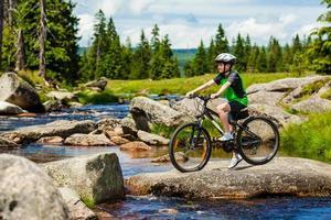 tonårspojke cyklar på skogsspår foto
