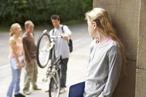 grupp vänner chatta medan en flicka tittar på. foto