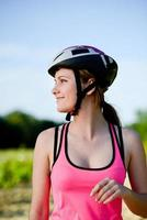 frisk glad ung kvinna ridning mountainbike utomhus på landsbygden foto