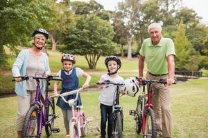 lyckliga morföräldrar med barnbarnen på cyklar foto
