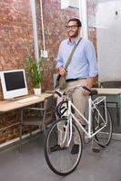 avslappnad affärsman med sin cykel foto