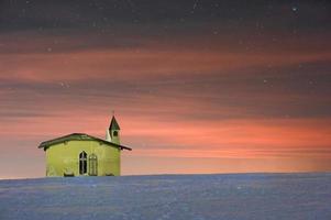 liten kyrka i bergen på natten. foto