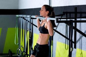 gymmet tårna att bar kvinnan pull-ups 2 barer träning foto