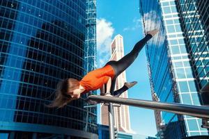 ung flicka som gör yoga utomhus i staden foto