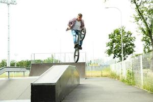 ung pojke hoppar med sin bmx cykel på skate park foto
