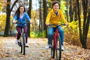 urban cykling - flicka och pojke som cyklar i stadsparken foto