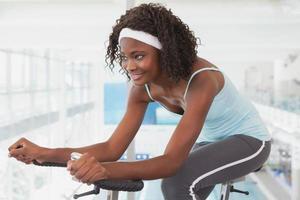 fit kvinna som tränar på motionscykeln foto
