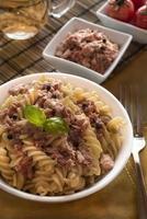 italiensk pasta med tonfisk, svarta paprika och tomater foto