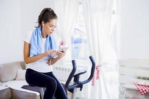 sportig kvinna träning på motionscykel i vardagsrummet foto
