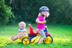 två små barn på en cykel i trädgården