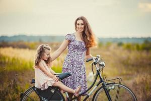 mamma med barnet och cykeln foto