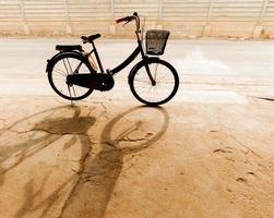 cykel som står på parkeringsplatsen och dess skugga foto