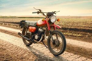 klassisk gammal motorcykel på en grusväg. foto