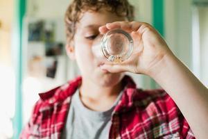 pojke som avslutar glas juice foto