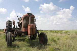 ca 1960-talets vintage-traktor i ett fält med logotyper borttagen foto