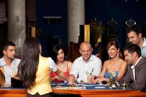 skrattande vänner spelar kort i ett kasino foto