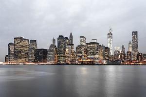 New York Citys finansiella distriktshorisont i skymningen foto