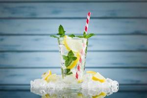 citronvatten i glas på blå träbakgrund foto