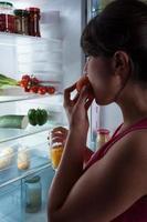 flicka äter persika foto