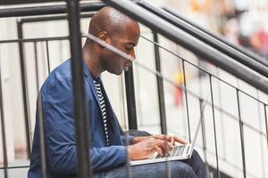 svart kille som använder anteckningsboken i New York foto