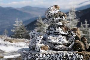 frusen inukshuk vid toppmötet i kaskadberg, adirondack park foto