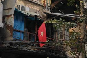 Vietnams flagga och gamla fattiga radhus foto