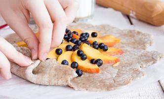 process för att förbereda kex med persika och blåbär foto