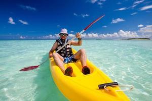 ung kaukasisk man som paddlar i havet på Maldiverna foto