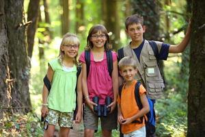 porträtt av fyra barn med campingutrustning