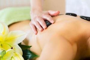 kvinna med wellness massage i varm sten foto
