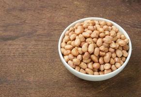 rå jordnötter i vit skål på träbord. foto