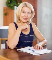 mogen kvinna undertecknar dokument foto