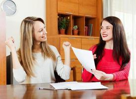 glada kvinnor med ekonomiska dokument foto