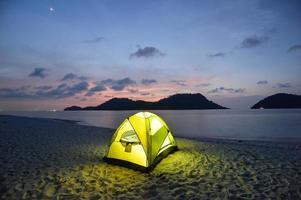 grönt tält på sandig vild strand vid skymningen foto