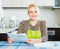 kvinna med dokument på köket foto