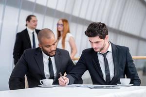 affärsman undertecknar dokument. två framgångsrika affärsmän som ler
