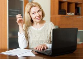 mogen kvinna med laptop och ekonomiska dokument foto