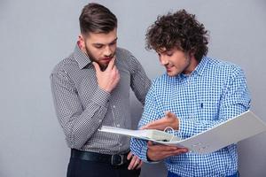 två tillfälliga affärsmän som läser dokument i mappen foto