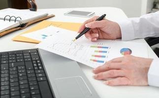 affärskvinna som arbetar med finansiella grafer foto