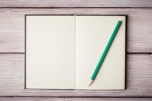 öppen anteckningsbok och en pancil på gamla träskrivbord