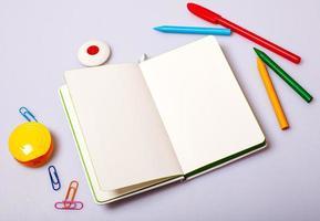 öppet anteckningsblock med tomma sidor på bordet med kontorsverktyg foto
