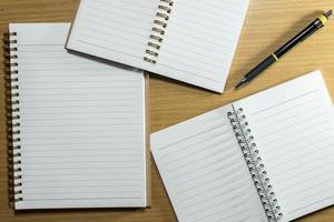 penna, penna och anteckningsbok på träbord. toppvy