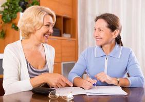 äldre damer undertecknar dokument foto