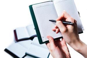 hand skriva på anteckningsboken på vit bakgrund foto