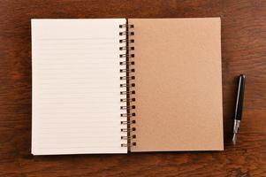 öppen anteckningsbok och penna
