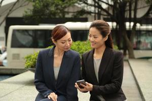 två damer diskuterar med smartphone foto